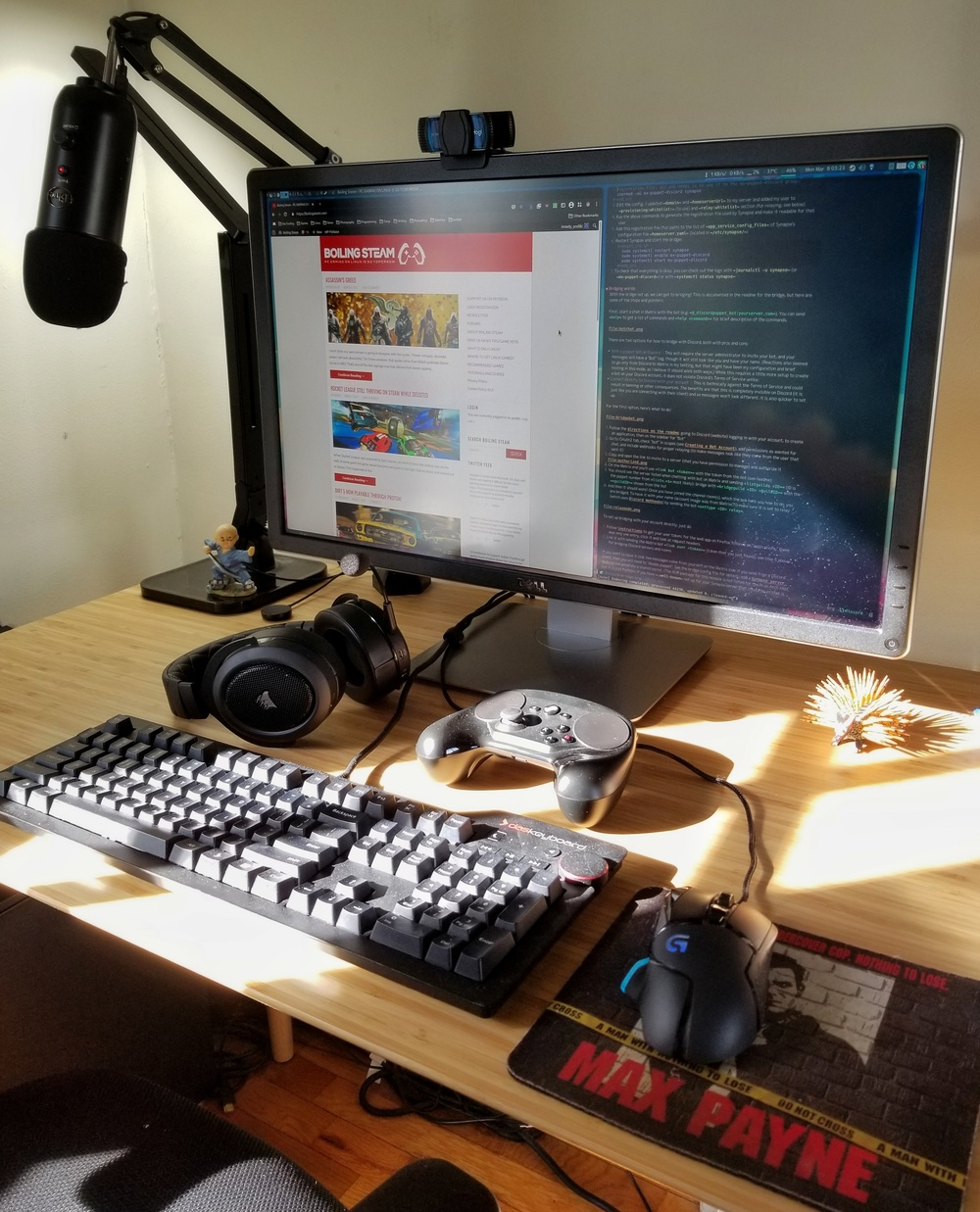 A picture of a wooden desk with computer monitor, keyboard, mouse, and other accessories. Podiki's gaming rig
