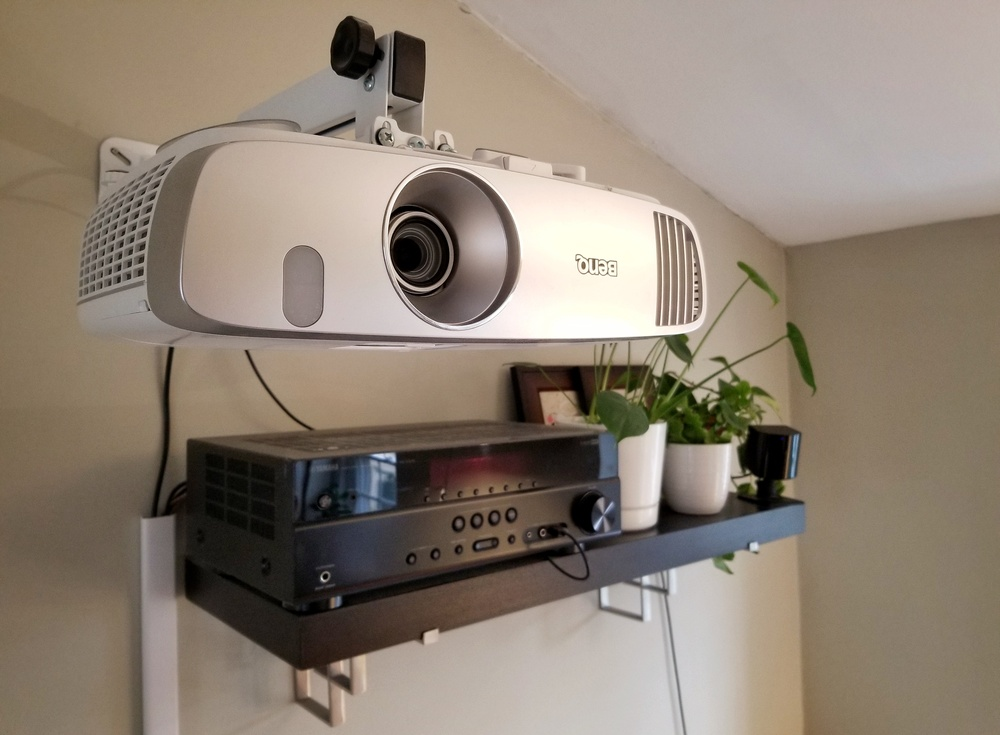 A projector by BenQ together with the VR sensor attached to the wall